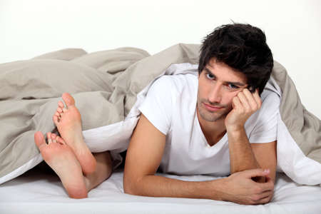 Annoyed man lying next to a woman in bed photo