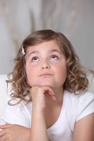 niño orando: Chica mirando hacia el techo Foto de archivo