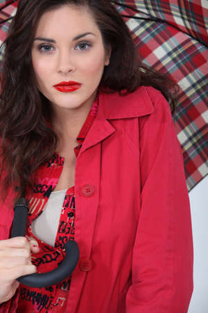 heavily: Heavily made-up woman with an umbrella