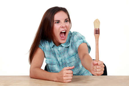 fracas: Woman arguing with a paintbrush Stock Photo