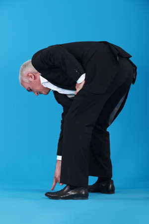bent over: Businessman bent over pointing at shoes Stock Photo
