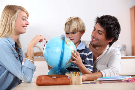 Little boy doing homework with his parents photo