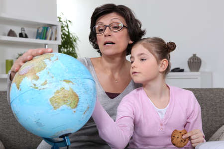Woman looking at a globe with her granddaughter photo
