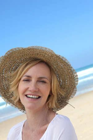 chapeau de paille: Sourire, femme dans un chapeau de paille sur la plage