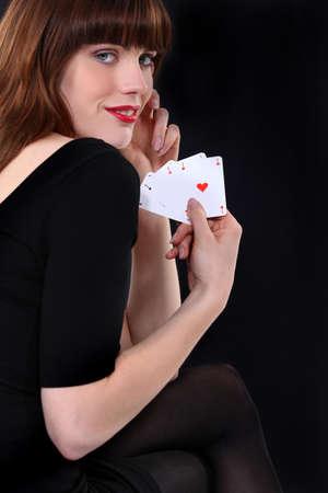 seductive woman: Woman holding four aces Stock Photo