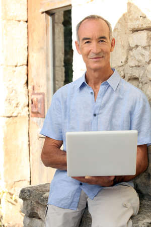 ail: Grey haired man sat on stone wall with laptop