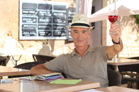 senior man toasting on a cafe terrace photo