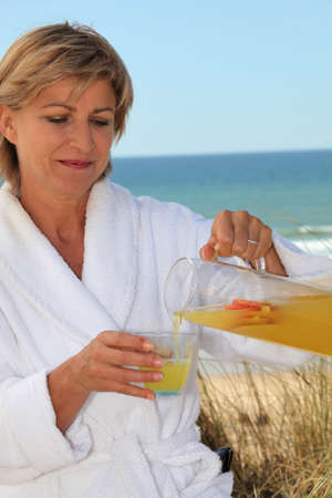 Woman by the sea pouring breakfast juice photo