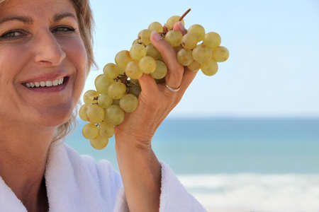 age 35 40 years: Woman eating a bunch of grapes by the sea