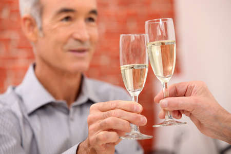 happy hour: A mature man toasting.