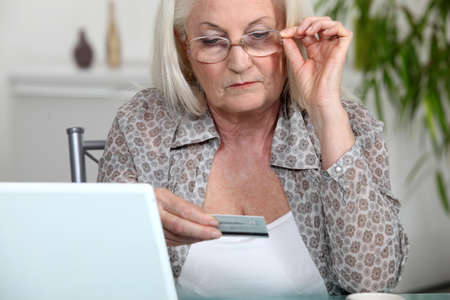 bankcard: Older woman using her credit card online