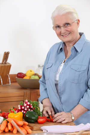 Elderly woman chopping vegetables Stock Photo - 11796707