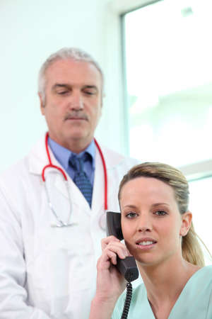 Nurse on the telephone whilst a doctor stands by Stock Photo - 11797533