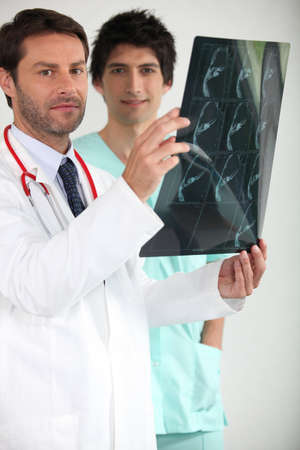 Doctor and male nurse examining x-ray image photo