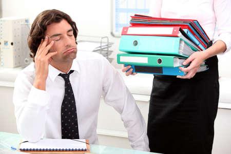 desk work: Office worker overwhelmed by load of work