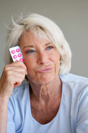 65 70 years: Woman fed up with taking her medication Stock Photo