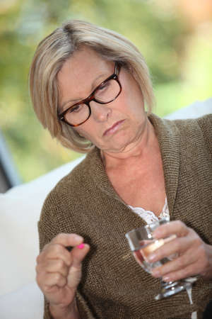 double chin: Woman taking a pill with water