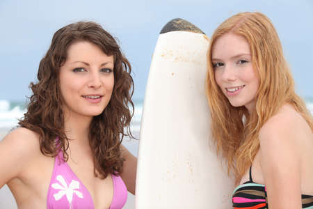 two girls on the beach with a surfboard photo