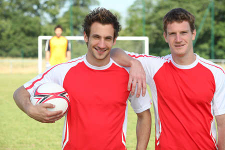 friends playing football posing together Standard-Bild