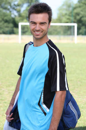 Smiling footballer with kitbag photo