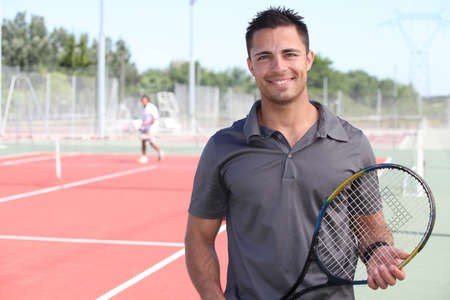 sports coach: tennis player posing in front of a tennis court