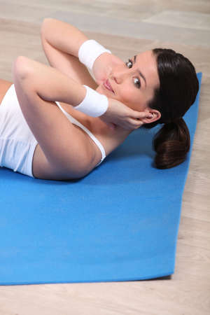 Pretty brown-haired woman doing situps photo