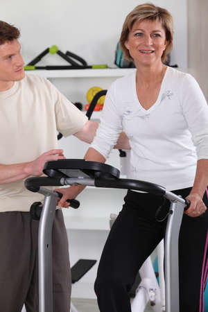 physical fitness: Woman with personal trainer in gym Stock Photo