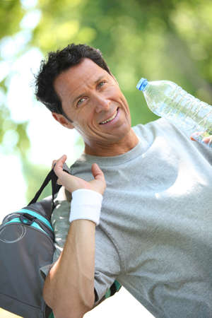 Sporty looking man drinking from a large bottle of water photo