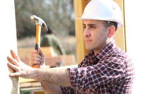 banging: Handyman hitting a nail with a hammer Stock Photo