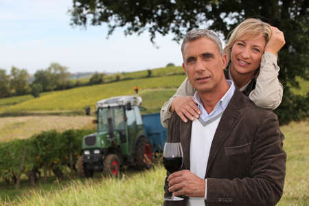40 years old: Couple drinking wine in a vineyard Stock Photo