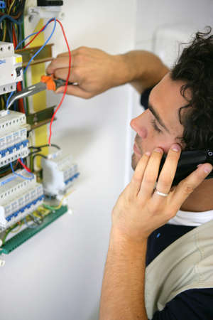 electric system: electrician working on the fuse board Stock Photo