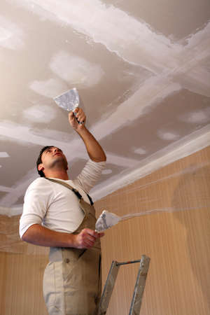 house renovation: Plasterer working on ceiling Stock Photo