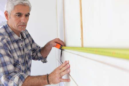 Man measuring wall photo