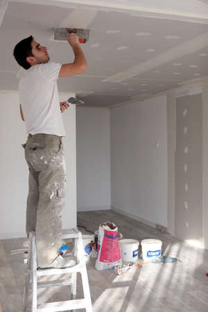 plastering: craftsman painting the ceiling