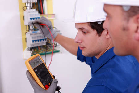 electrical wire: Two technical engineers checking electrical equipment Stock Photo