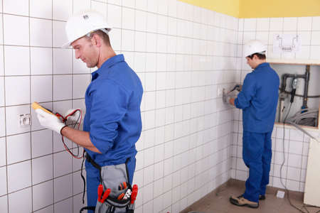 electrics: Workteam installing electrics in a tiled room