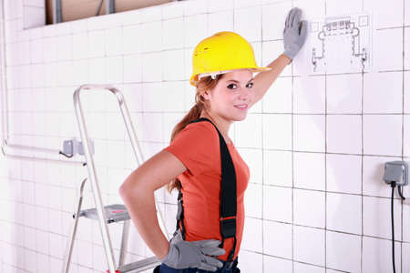 woman engineer: Young woman laborer leaning on a wall