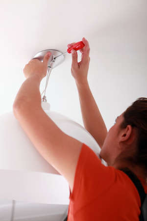 screw driver: Young woman fitting a light Stock Photo