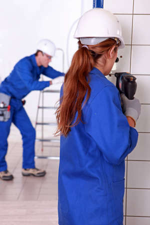 Female electrician drilling a wall photo