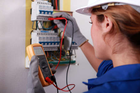 fusebox: Female electrician taking reading from fuse box Stock Photo