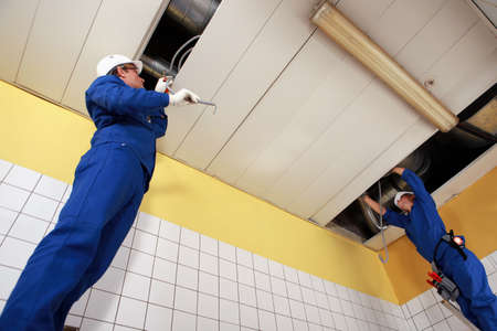 Two laborers working on ceiling piping photo