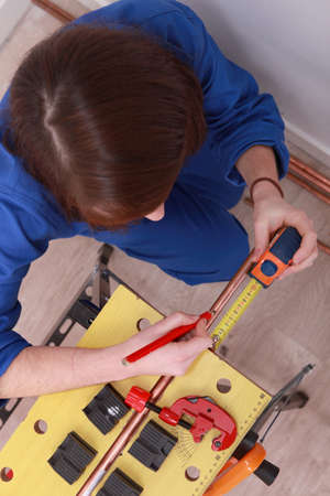 jumpsuite: a female technician working on a copper tube