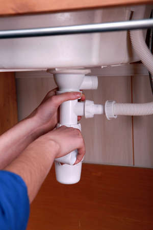 Plumber fitting the waste pipe to a kitchen sink photo