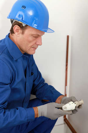 Plumber with a radiator valve photo