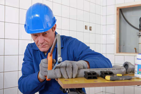 boiler suit: Builder sawing a tube