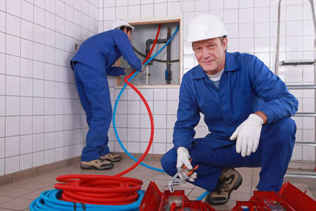 jumpsuite: two plumbers working, one plumber is connecting pipes