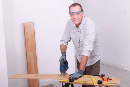 Man cutting floorboard Stock Photo - 11823765