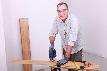 Man cutting floorboard Stock Photo - 11823765