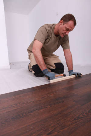 Man laying a wooden floor photo