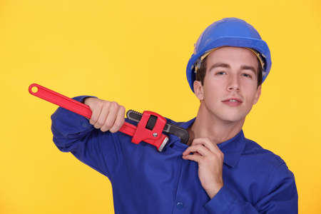dauntless: portrait of young plumber holding adjustable spanner against yellow background